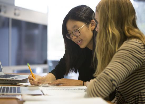 Two women at a desk looking over classwork